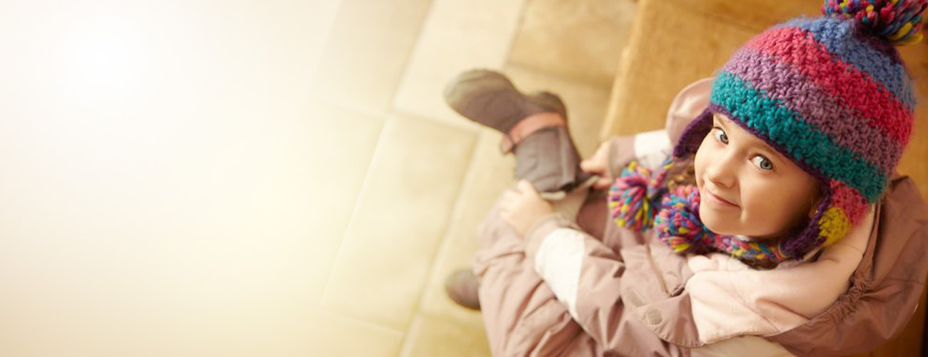Girl sitting on tile with winter clothing